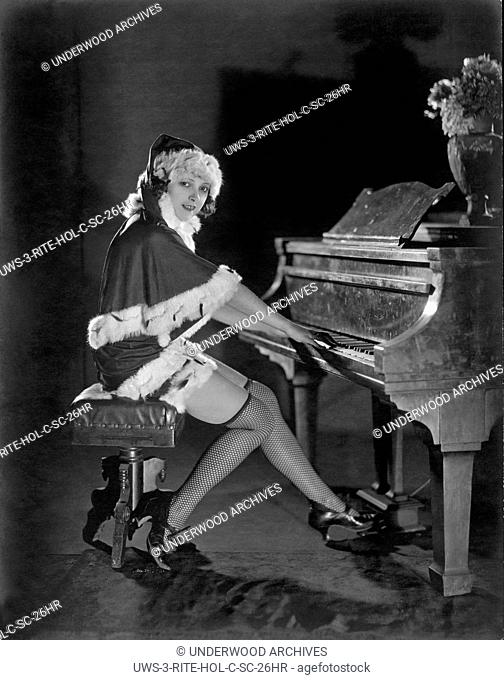 Hollywood, California: c. 1917 A Mack Sennett actress dons a Santa Claus outfit with fishnet stockings to play Christmas carols on a piano