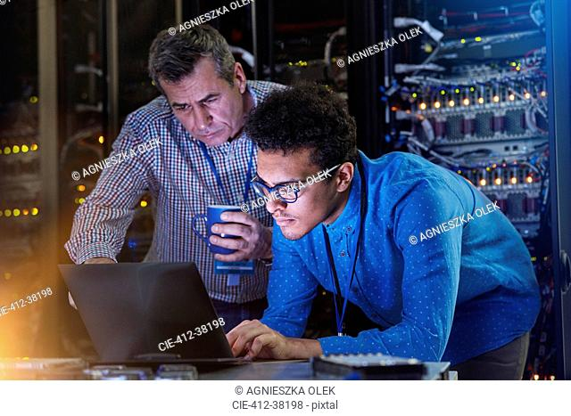 Focused male IT technicians working at laptop in dark server room
