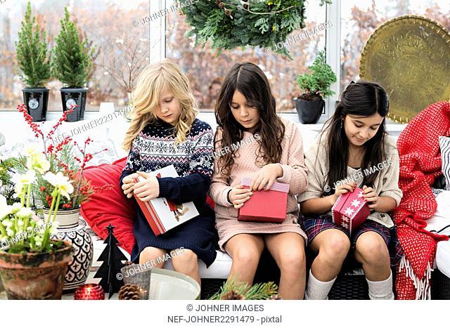 Three girls opening presents