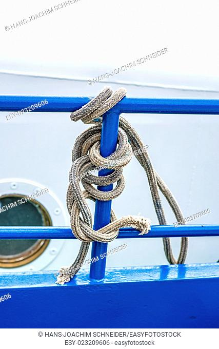 rope on a blue reling of a trawler