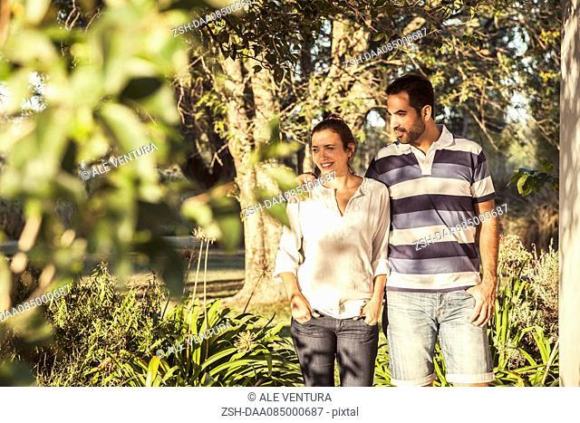 Couple walking through botanical garden looking at view