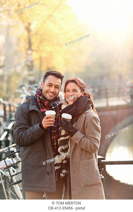 Portrait smiling young couple drinking coffee along urban autumn canal