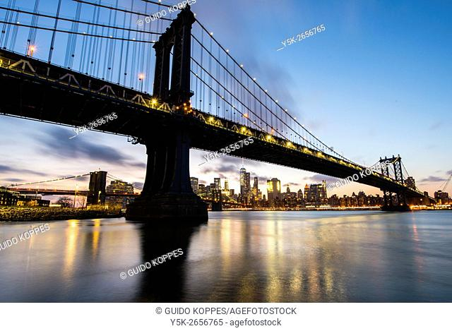 New York City, USA. Night time view at the Manhattan and Brooklyn Bridge and the East River from Juhn Street Park