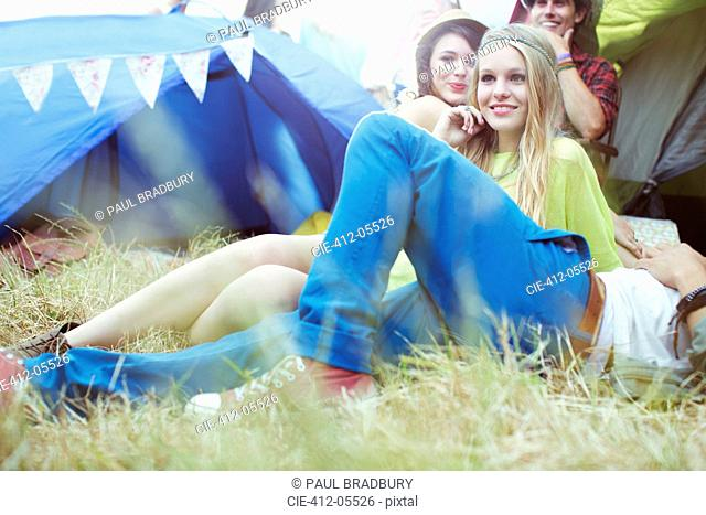 Friends relaxing outside tents at music festival