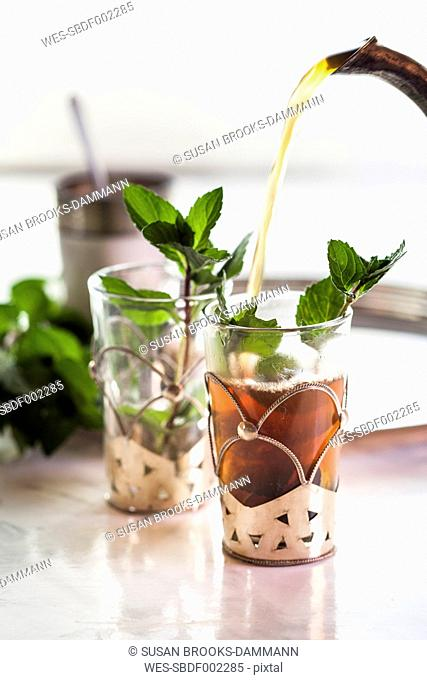 Pouring black tea into traditional North African tea glass with fresh mint leaves