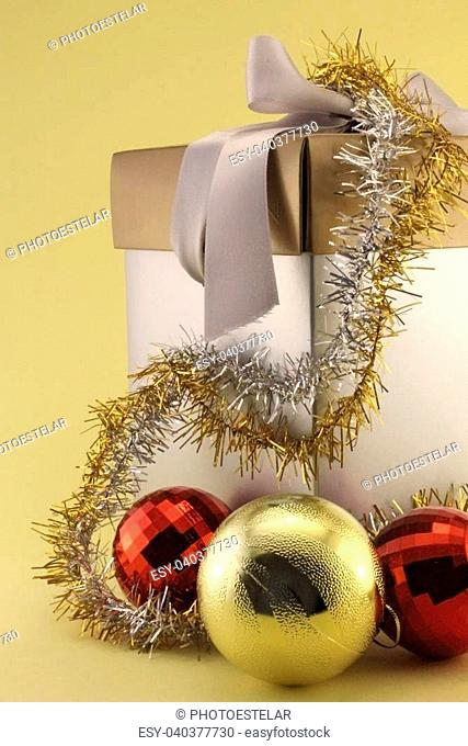 Christmas Gift Box, plated with gold cap. Ribbon and bow. Christmas balls and red gold, silver and gold garlands
