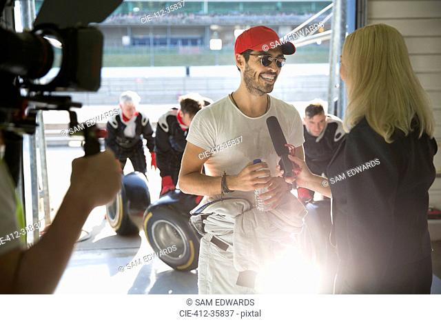 Female news reporter interviewing male formula one race car driver in repair garage