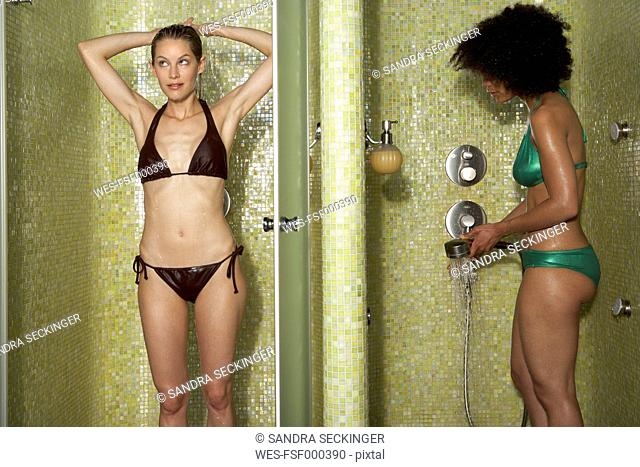 Two women standing in shower cabinets
