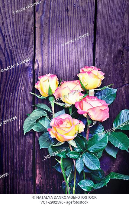 Bouquet of blossoming roses on a brown wooden background, vintage toning