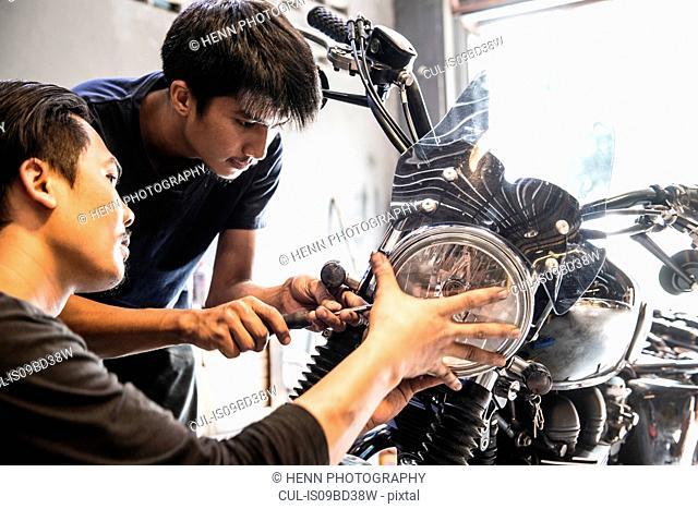 Mechanics working at custom motorbike shop, Bangkok, Thailand