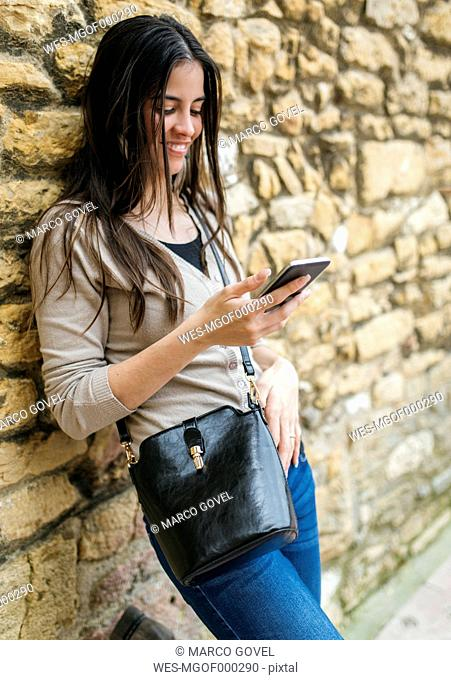 Young woman leaning against stone wall looking at smartphone