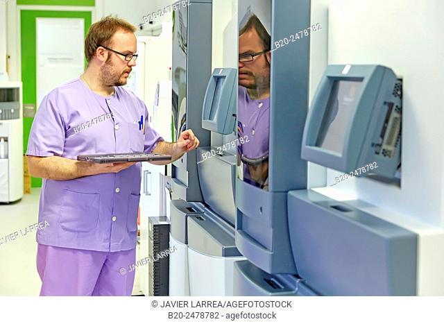 Laboratory worker looking at microscope slide strainer monitor at hospital, Histology, Anatomic Pathology, Hospital Donostia, San Sebastian, Basque Country