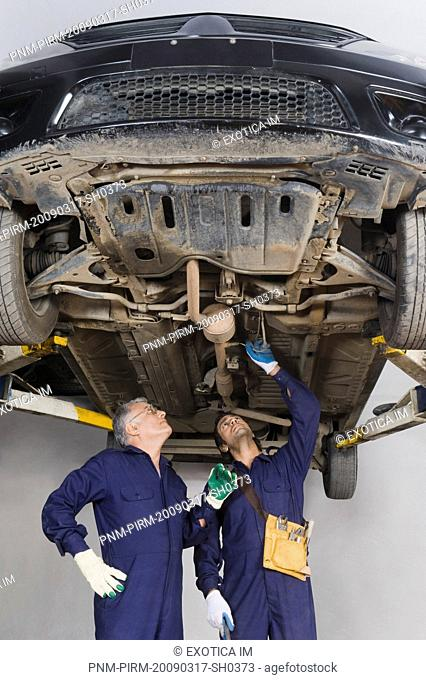 Auto mechanic with an apprentice working under a raised car in a garage