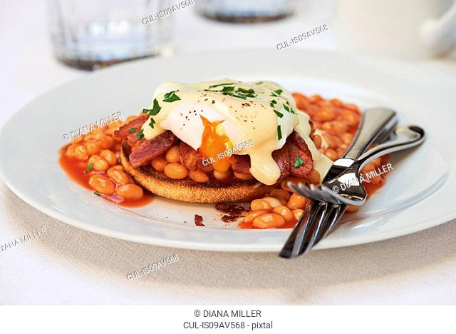 Poached egg, bacon and beans with hollandaise sauce on english muffin
