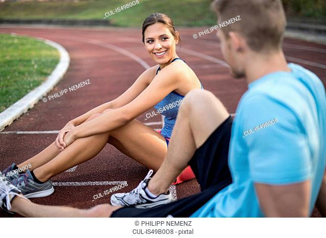 Young man and woman sitting on sports track, talking, smiling