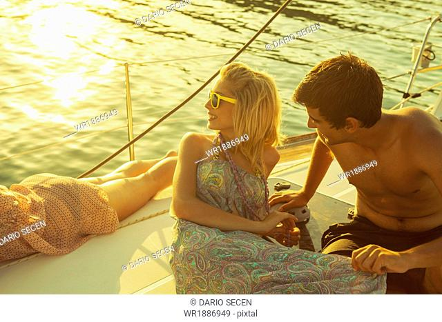 Croatia, Adriatic Sea, Young people on sailboat at sunset