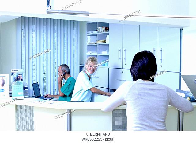 female patient and female medical assistant at the reception - male doctor at the background