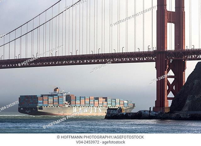 Large container ship passing under the Golden Gate Bridge, San Francisco, California, USA