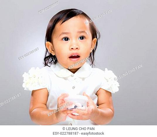Asian baby girl confuse and hold plastic box