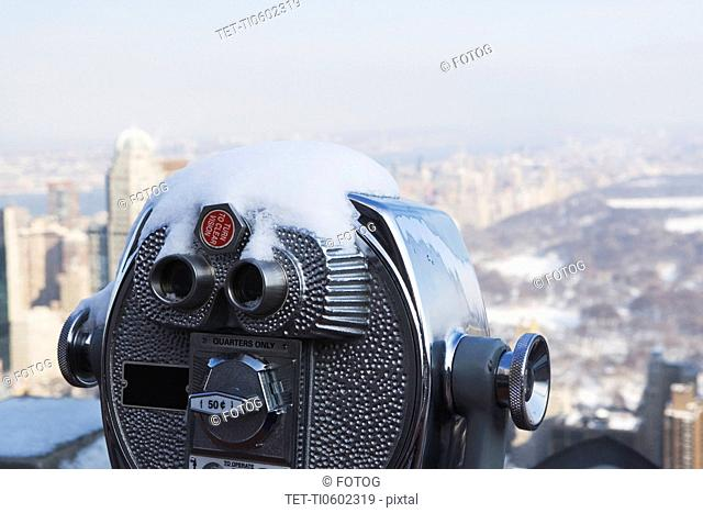 USA, New York City, Coin operated binoculars covered with snow, Central Park in background