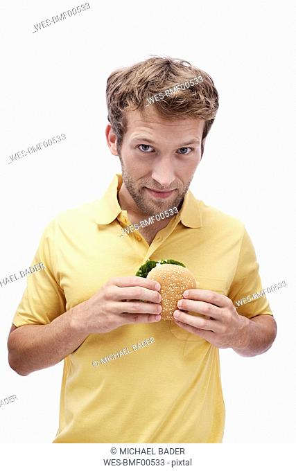 Young man holding Hamburger, portrait