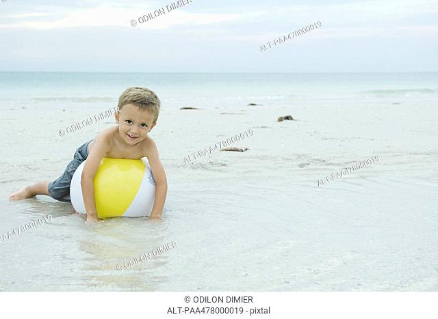 Little boy lying on beach ball, smiling at camera, full length