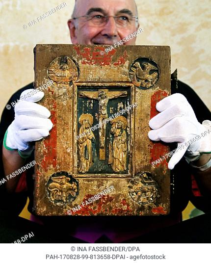 Bishop Felix Genn holds up the Liesborn Evangelion ('Liesborner Evangeliar') during its official presentation at the Museum Liesborn Abbey in Wadersloh, Germany