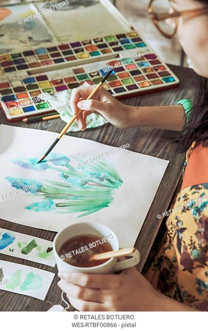 Young woman painting plants with water colors