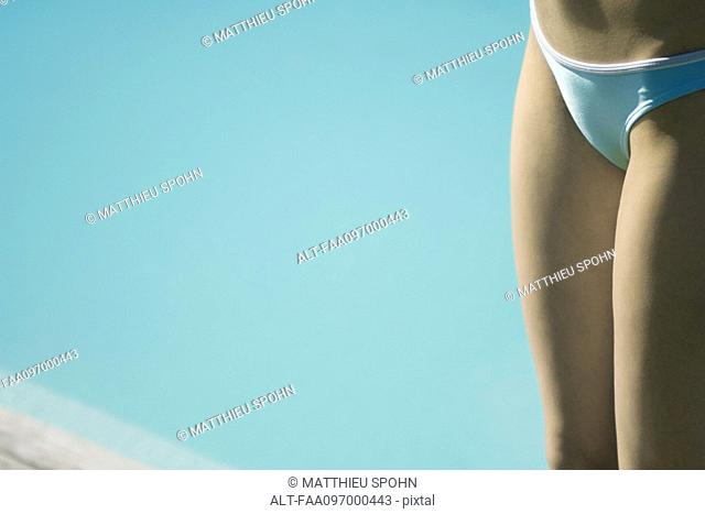 Woman by pool in bikini, clos-up of mid section