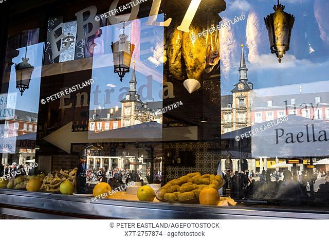 The Plaza Mayor Reflected in the window of a cerveceria and Tapas bar, Plaza Mayor, Madrid, Spain