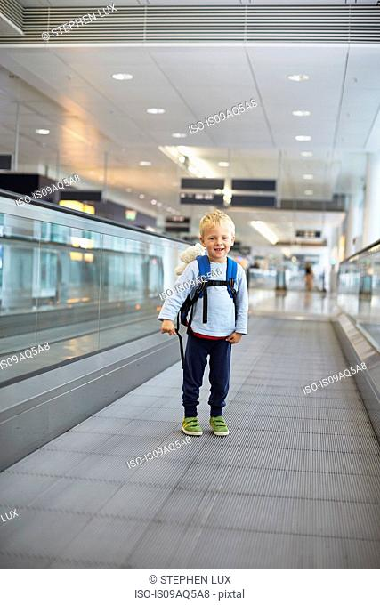 Portrait of cute boy on moving walkway at Munich Airport, Germany