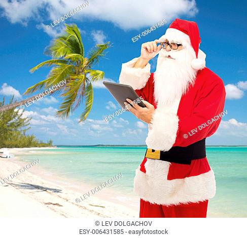 christmas, holidays, travel, technology and people concept - man in costume of santa claus with tablet pc computer over tropical beach background