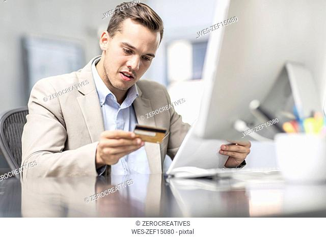 Businessman shopping online at desk in office