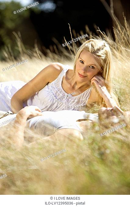 A young woman lying on the grass with her boyfriend