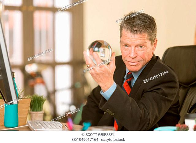 Confident professional man with a crystal ball