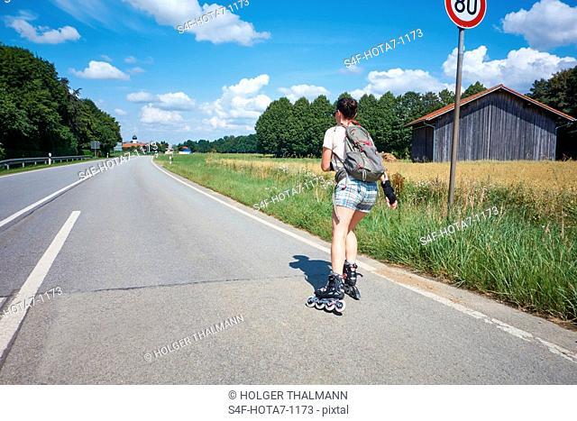 Deutschland, Bayern, Frau fährt Inlineskates auf einer Landstraße