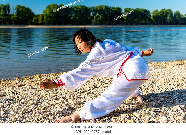 Women practicing tai chi by a lake