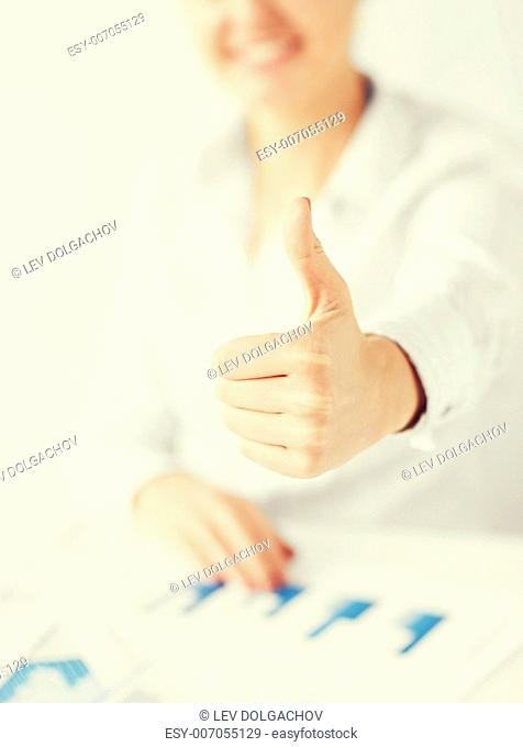 business, office, school and education concept - happy woman with charts, papers and thumbs up