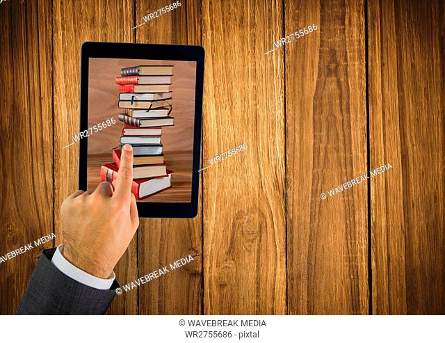 Hand touching tablet showing book pile on table