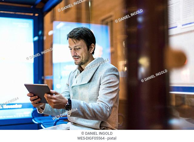 Businessman with digital tablet sitting at a bus stop at night