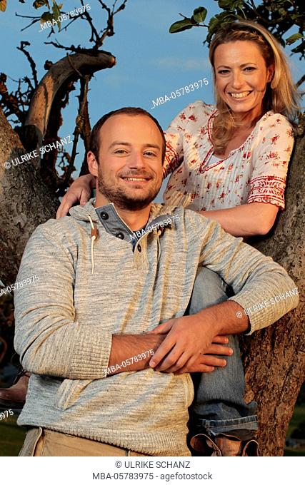 Couple, young, smiling, tree, climbing, half portrait