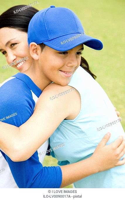 Mother hugging son in baseball gear