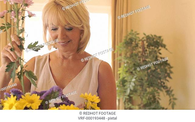 Senior couple indoors flower arranging