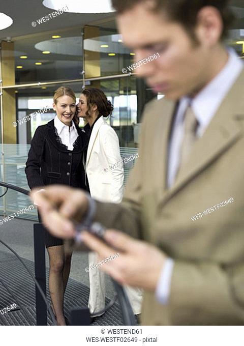 Two businesswomen whispering, man using palmtop (focus on background)