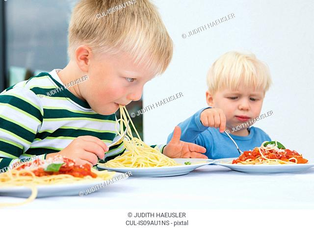 Boy and toddler brother eating spaghetti on patio
