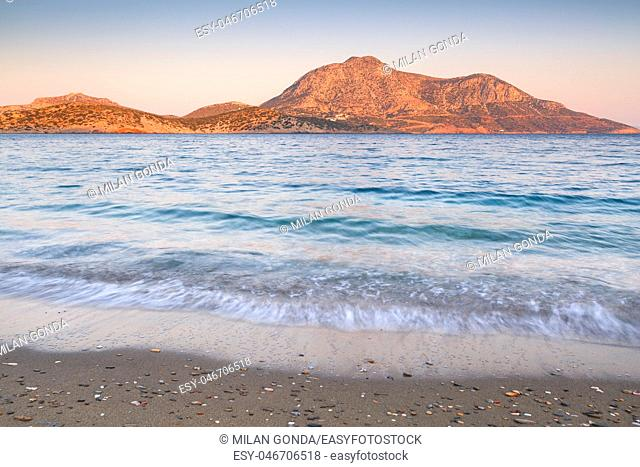 Beach in the town of Fourni and view of Thymaina island early in the morning, Greece.