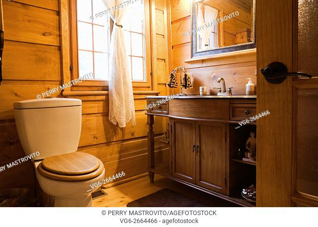 Bathroom inside a Canadiana cottage style residential stacked white pine log home, Laurentians, Quebec, Canada