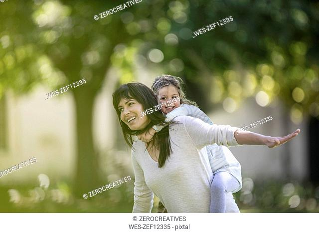Mother swinging her daughter in garden