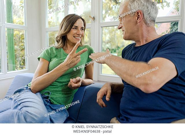 Happy mature couple sitting on couch at home playing Scissors Paper Stone