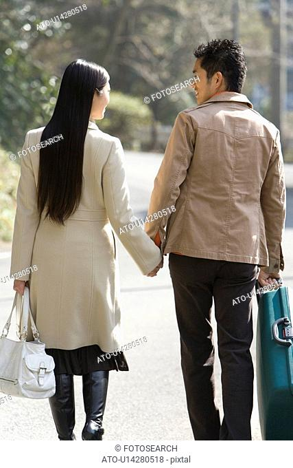 Japanese couple walking hand in hand, rear view, Japan